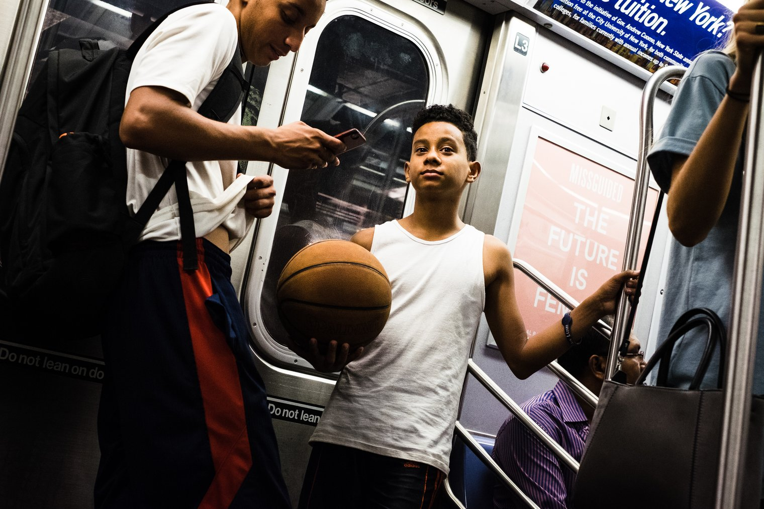 A kid with a basketball on the subway