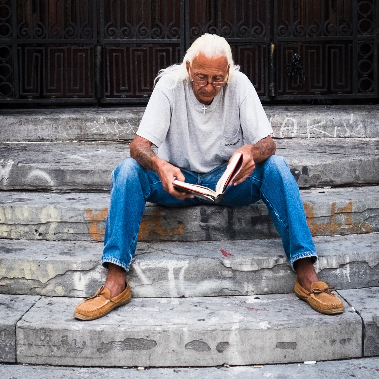 A man sitting on stairs reading a book